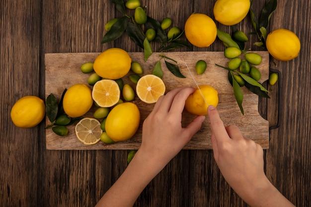 Vista superior de manos femeninas cortando limones frescos en una tabla de cocina de madera con cuchillo con kinkans aislado en una superficie de madera