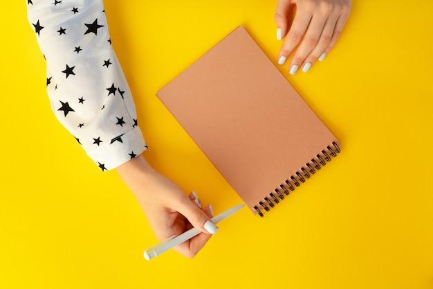 Vista superior de manos femeninas escribiendo en el cuaderno