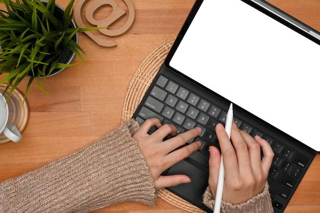 Vista superior de manos femeninas escribiendo en el teclado de la tableta en el trazado de recorte del espacio de trabajo de madera simple
