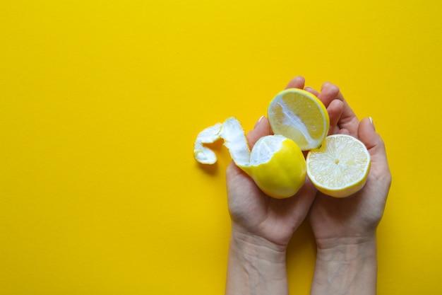 Vista superior de manos femeninas con limones maduros enteros y en rodajas sobre una superficie amarilla, concepto de salud y vitaminas