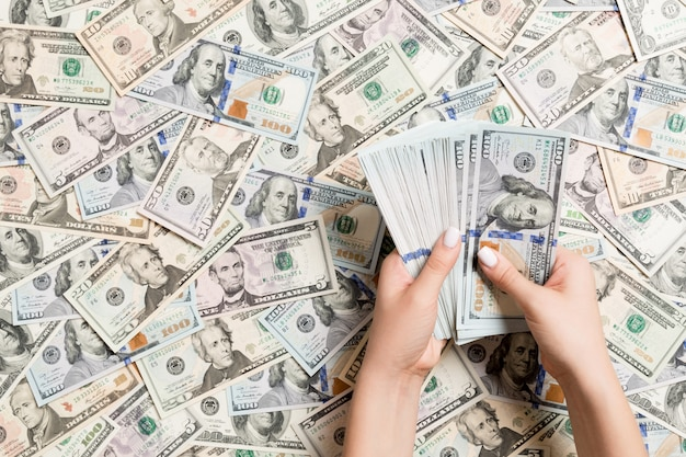 Vista superior de las manos femeninas que cuentan el dinero en fondo del dólar.