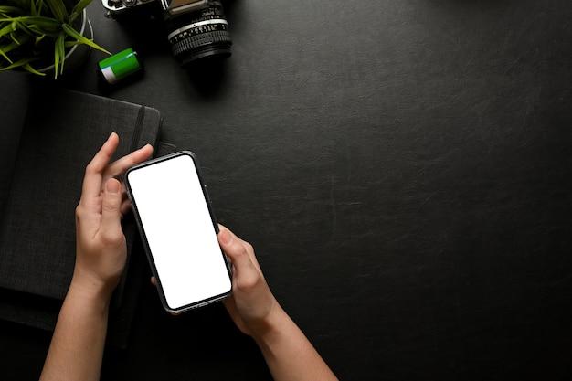 La vista superior de las manos femeninas que usan el teléfono inteligente incluye la pantalla de la ruta de recorte en el espacio de trabajo creativo oscuro con cámara y material de oficina