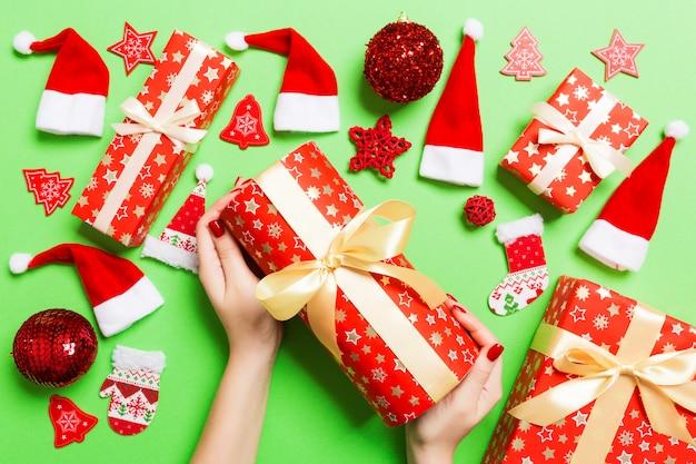 Vista superior de manos femeninas con un regalo de navidad en verde festivo.
