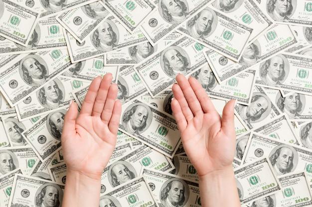 Vista superior de manos femeninas sobre fondo de dólar. concepto de riqueza con espacio vacío para su diseño. mendigando el concepto de dinero