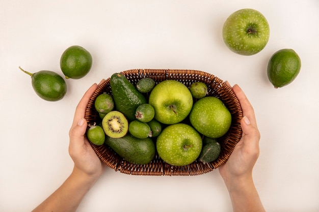 Vista superior de manos femeninas sosteniendo un balde de frutas frescas como manzanas, feijoas y aguacate sobre una superficie blanca