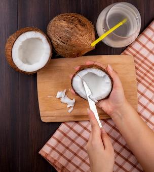 Vista superior de las manos femeninas sosteniendo el coco en una mano y cortando en la otra mano sobre una tabla de cocina de madera con cocos y un vaso de agua sobre un mantel a cuadros en negro