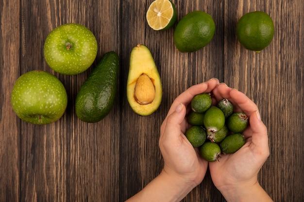 Vista superior de manos femeninas sosteniendo feijoas frescas con limones de manzanas verdes y aguacates aislado en una pared de madera