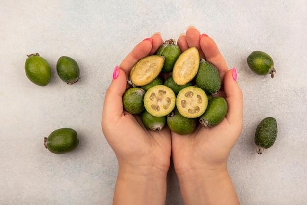 Vista superior de manos femeninas sosteniendo una mitad madura tropical y feijoas enteras con feijoas aisladas sobre una superficie gris