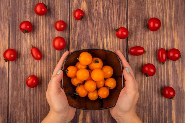 Vista superior de manos femeninas sosteniendo un tazón de tomates cherry naranja sobre una superficie de madera