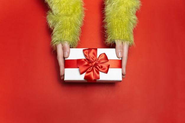 Vista superior de manos femeninas en suéter verde, sosteniendo una caja de regalo blanca con cinta roja sobre fondo de color rojo.