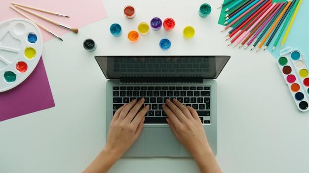 Vista superior de manos femeninas usando una computadora portátil y varias herramientas de dibujo coloridas