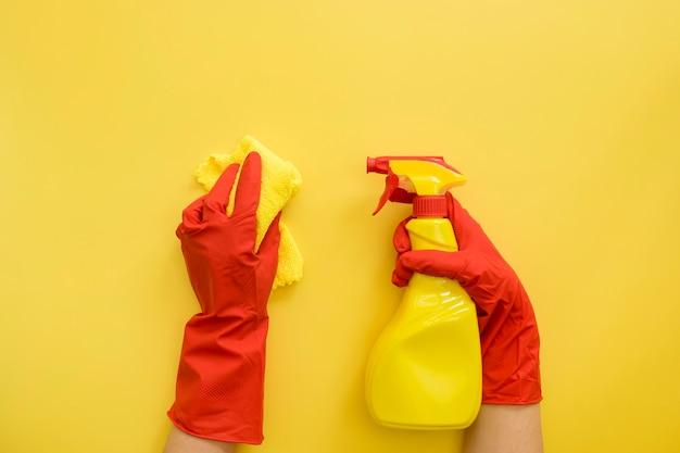 Vista superior de las manos con guantes de goma con productos de limpieza