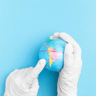 Vista superior de manos con guantes quirúrgicos sosteniendo globo terráqueo