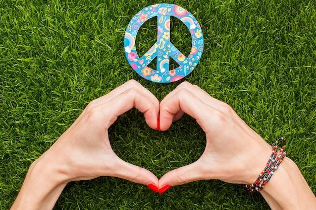 Vista superior de manos haciendo corazón con signo de paz