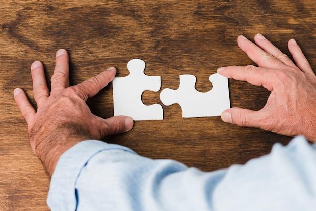 Vista superior manos haciendo puzzle sobre mesa de madera
