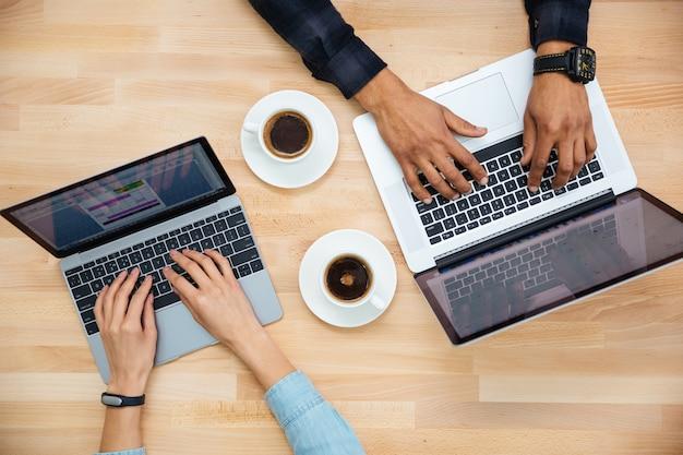 Vista superior de las manos del hombre africano y la mujer caucásica escribiendo en dos computadoras portátiles y tomando café en la mesa de madera