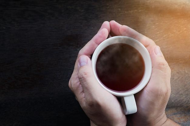 Vista superior de las manos del hombre que sostienen la taza de café caliente