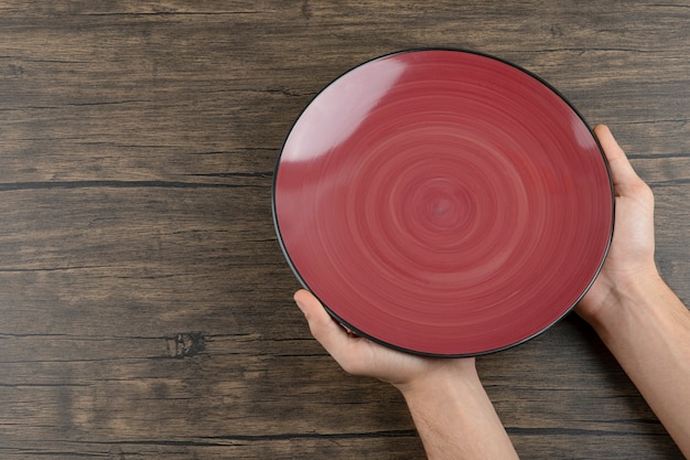 Vista superior de las manos del hombre sosteniendo un plato rojo vacío sobre una mesa de madera.