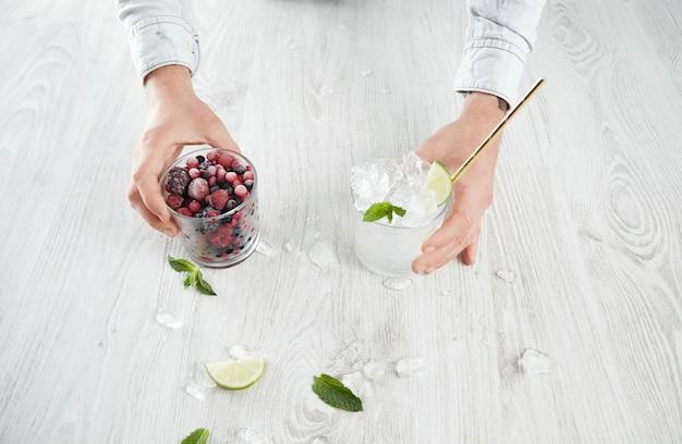 Vista superior de las manos del hombre sostienen vasos con bayas congeladas y cubitos de hielo con limón