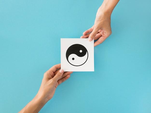 Vista superior de manos intercambiando símbolos ying y yang