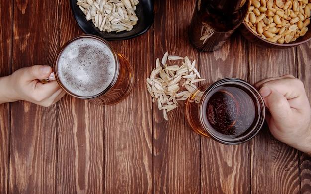 Vista superior de manos con jarras de cerveza y aperitivos salados semillas de girasol en madera rústica