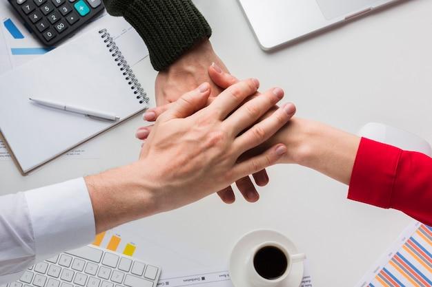 Vista superior de las manos juntas sobre el escritorio