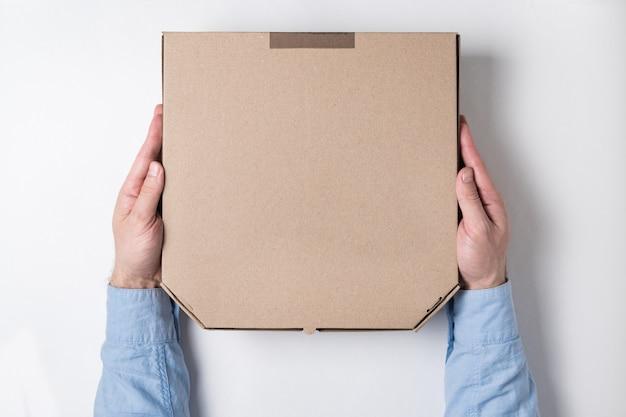 Vista superior de manos masculinas y caja de pizza en blanco