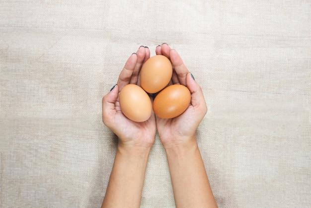 Vista superior de las manos de la mujer joven, sosteniendo los huevos en las manos en el saco