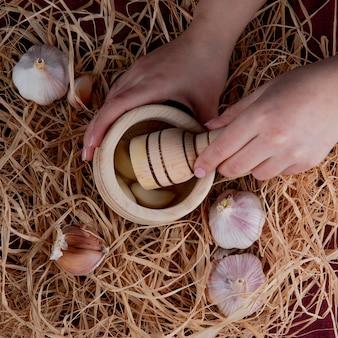 Vista superior de manos de mujer presionando dientes de ajo en trituradora de ajo y bulbos de ajo alrededor sobre fondo de paja