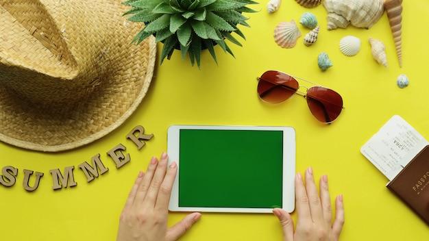 Vista superior de las manos de mujer sosteniendo tableta digital con pantalla verde, accesorios de verano. fondo de playa de vacaciones de verano, concepto de verano de viaje