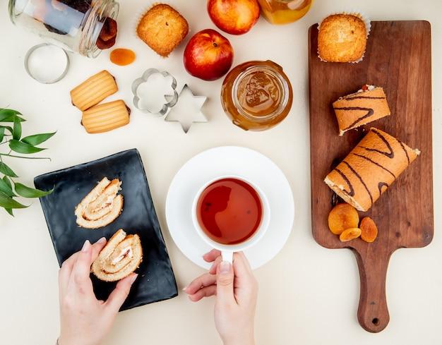 Vista superior de manos de mujer sosteniendo una taza de té y una rebanada de rollo con mermelada, galletas, pasas y ciruelas secas en mesa blanca