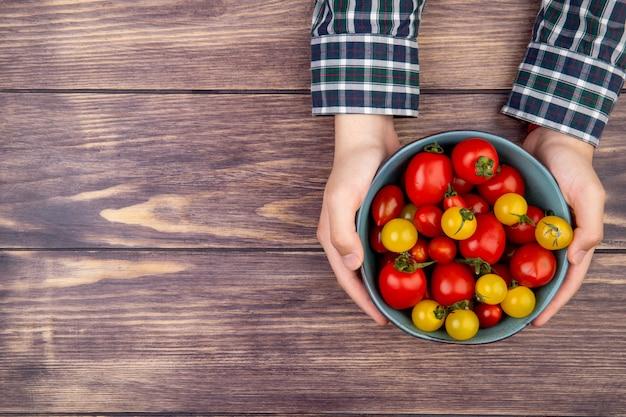 Vista superior de manos de mujer sosteniendo un tazón de tomates en la mesa de madera