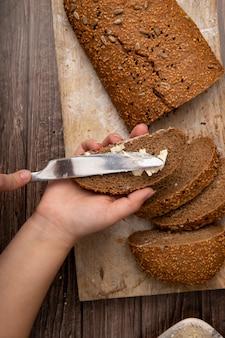 Vista superior de manos de mujer untando mantequilla sobre pan y rebanadas de pan sobre superficie de madera y fondo