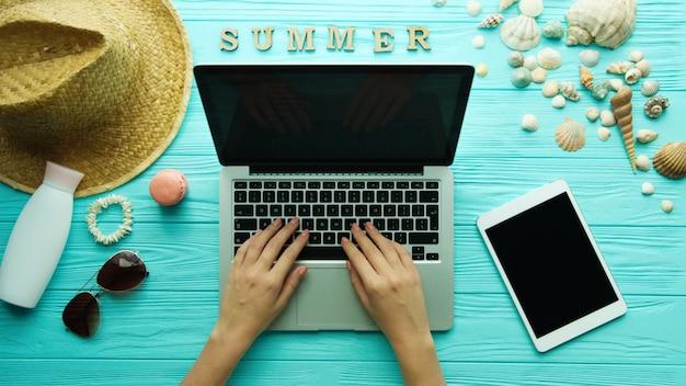 Vista superior de las manos de mujer usando la computadora portátil, accesorios de verano. fondo de playa de vacaciones de verano, concepto de verano de viaje