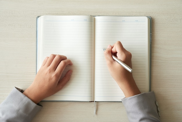 Vista superior de las manos de una persona irreconocible lista para completar el planificador