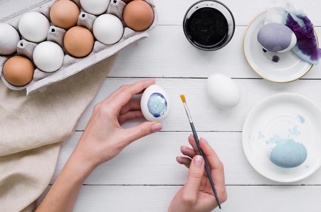 Vista superior de manos pintando huevo para pascua con cartón y tinte