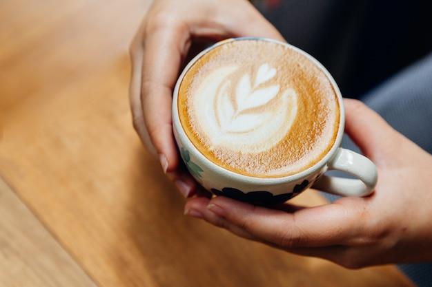 La vista superior de las manos que llevan a cabo una forma del corazón del arte del latte sirvió en taza de cerámica en la tabla de madera.