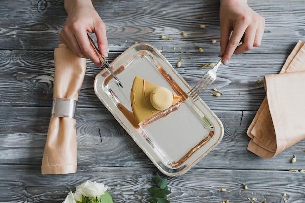 Vista superior de las manos que van a comer postre, pastel de mousse amarillo con almendra dacquoise, frambuesa confitada, capa crujiente con avellanas caramelizadas y polvo de frambuesa