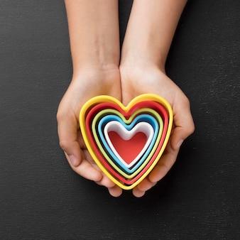 Vista superior manos sosteniendo elementos en forma de corazones