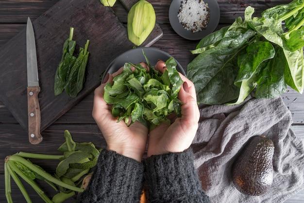 Vista superior manos sosteniendo ensalada orgánica