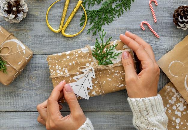 Vista superior de manos sosteniendo envuelto regalo de navidad con bastones de caramelo