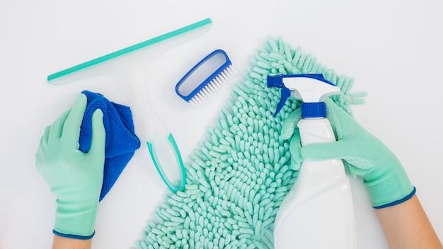Vista superior manos sosteniendo equipos de limpieza
