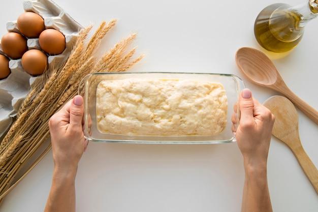 Vista superior manos sosteniendo molde de pastel con masa