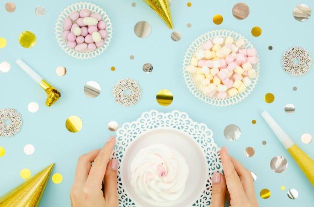 Vista superior manos sosteniendo un plato con muffin