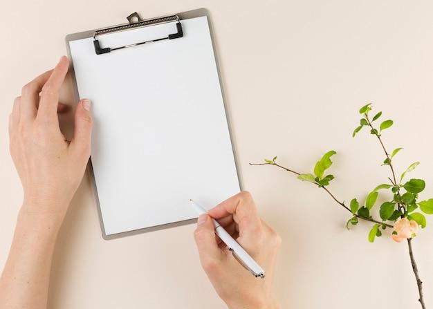 Vista superior de manos sosteniendo la pluma y el bloc de notas en el escritorio