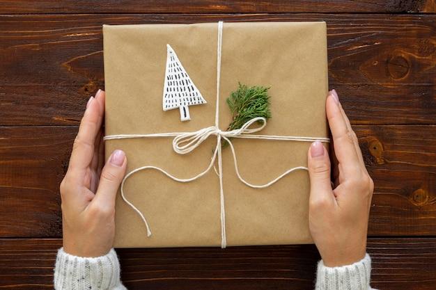 Vista superior de manos sosteniendo regalo de navidad