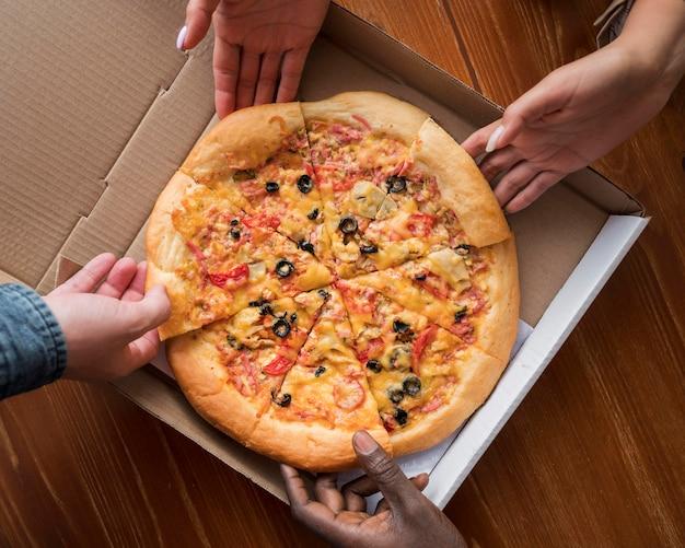 Vista superior de las manos tomando porciones de pizza