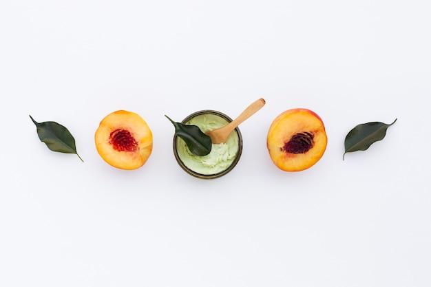Vista superior de manteca corporal y nectarinas sobre fondo liso