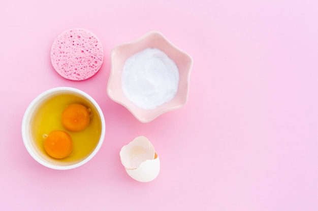 Vista superior de mantequilla corporal y huevos sobre fondo rosa