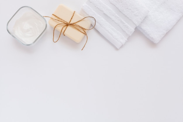 Vista superior de mantequilla corporal y jabón sobre fondo liso con espacio de copia